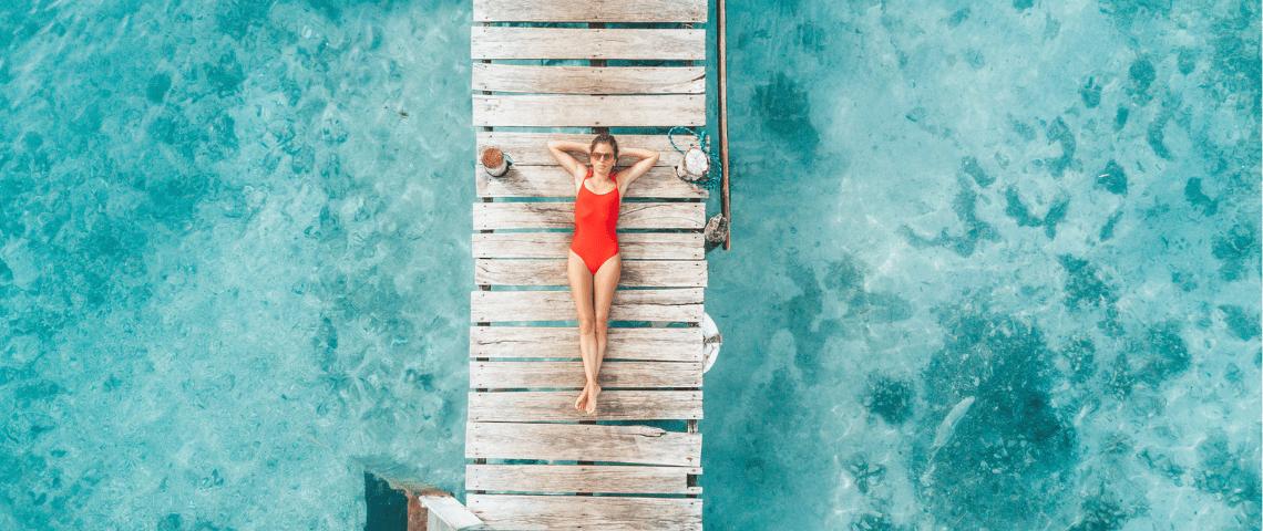 Une femme en maillot de bain rouge bonze sur un ponton vue du ciel