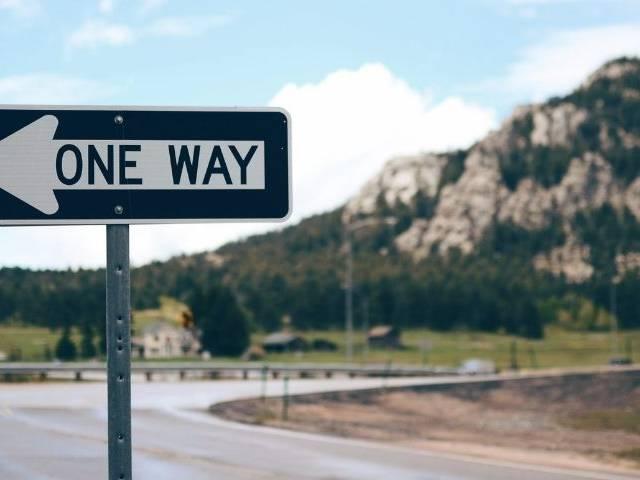 Un panneau - one way - devant une montagne