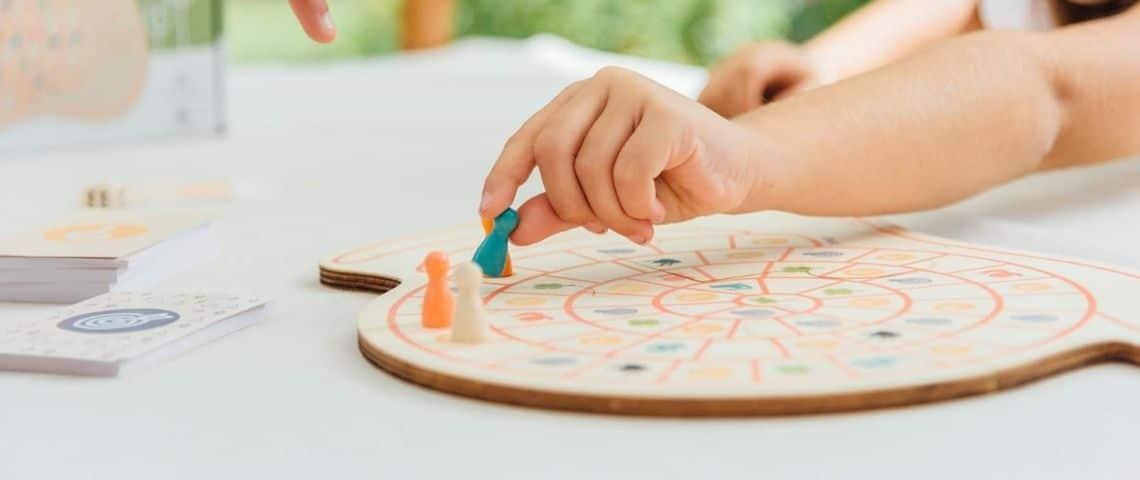 Enfant déplaçant un pion sur un plateau de jeu en bois