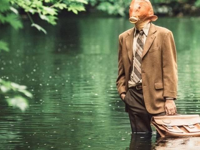 Un home-poisson en costume debout dans l'eau