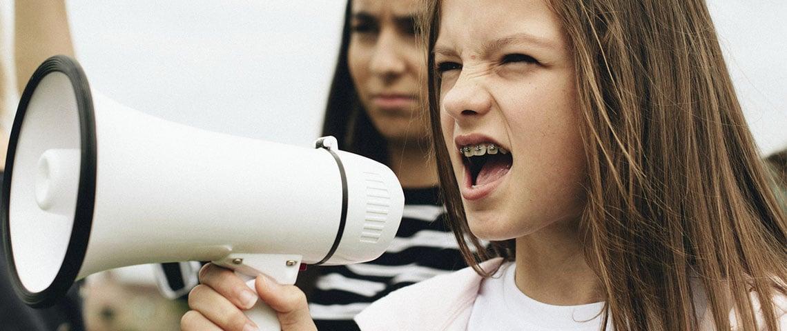 Jeune fille portant des bagues crie ans un mégaphone