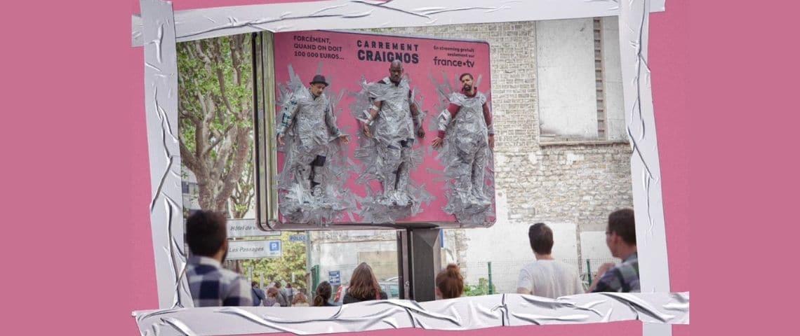Des hommes scotchés à un panneau publicitaire (humour)