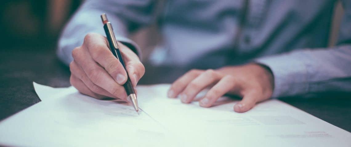un homme signe un papier
