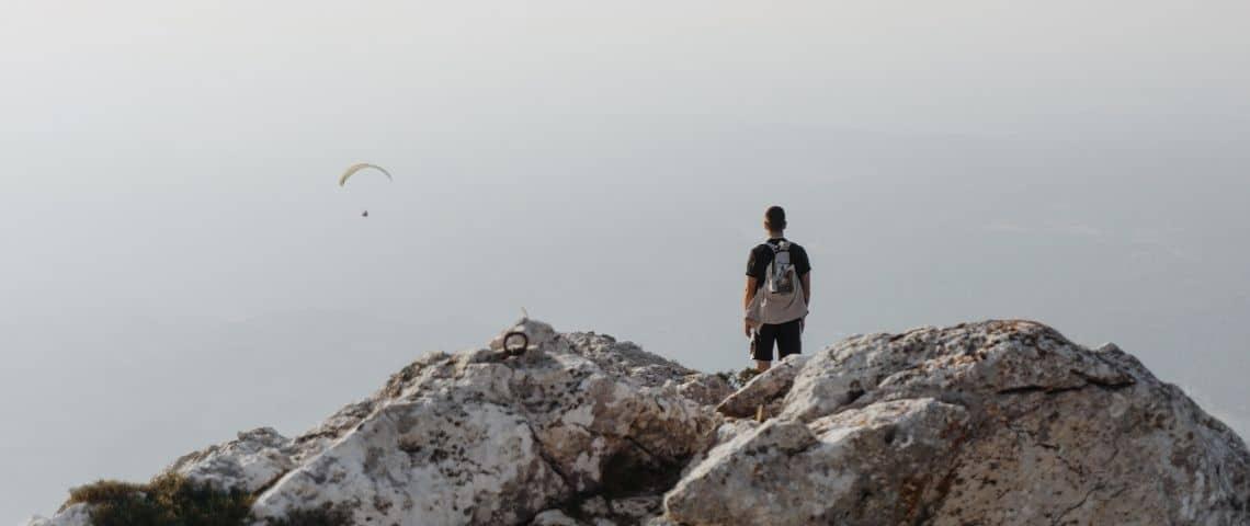 Un homme en haut d'une montagne. Il regarde au loin