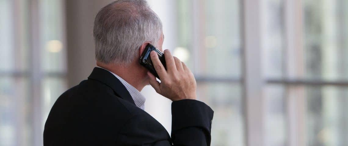 Un homme au téléphone. Il est en costume. Bureau