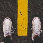 Des pieds. Chaussures : converses blanches. Bitume face une ligne de peinture jaune