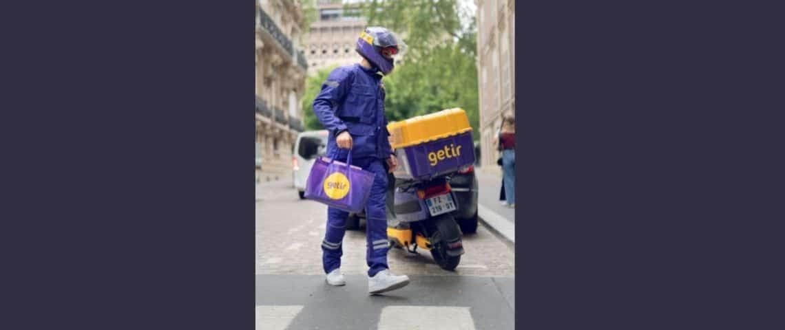 Un livreur à domicile à coté de son scooter
