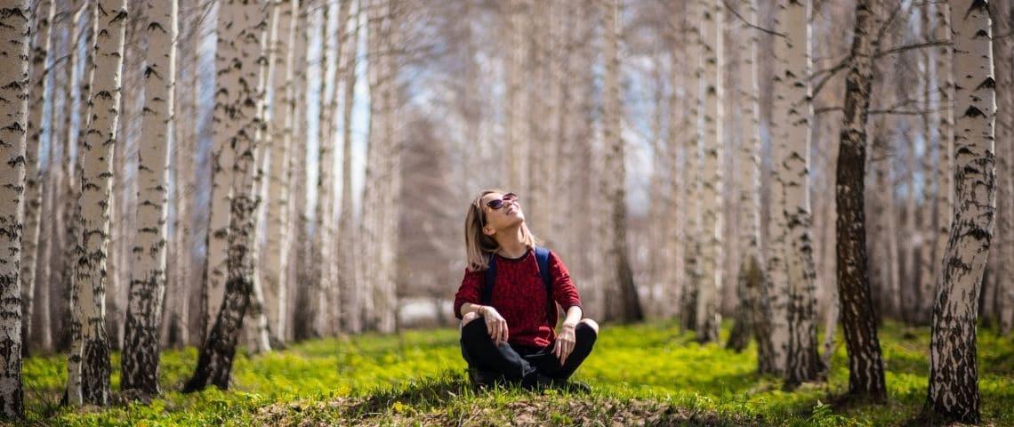 jeune femme assise dans l'herbe regardant le ciel