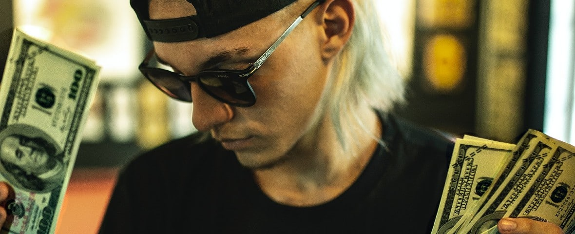 Un homme blond tient des billets dans ses mains