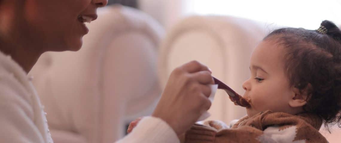 Mmaan donnant à manger à son enfant à la petite cuillère