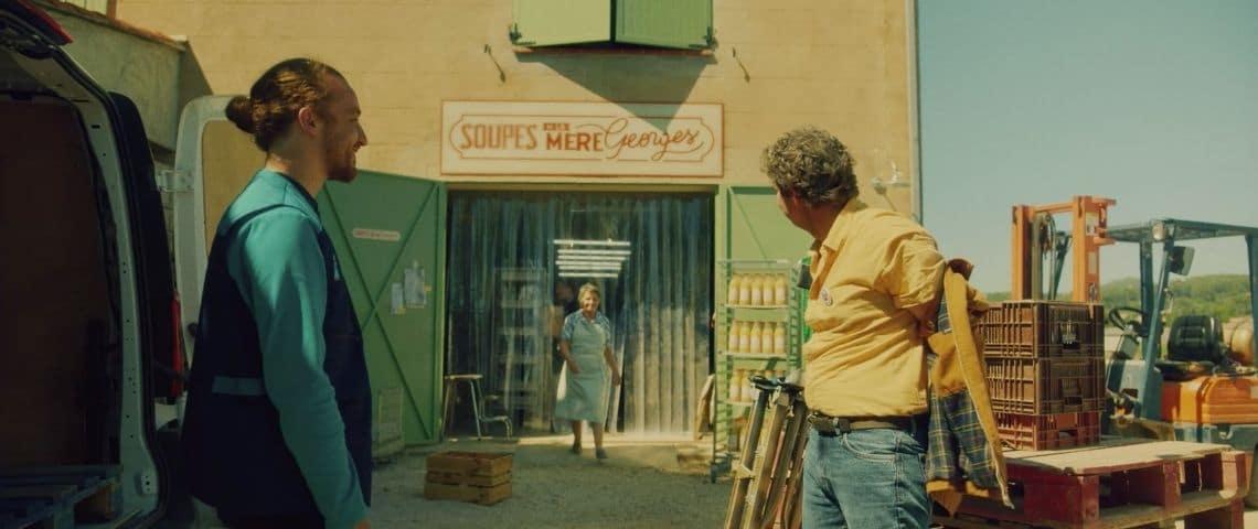 Femme sortant de sa boutique avec 2 hommes devant