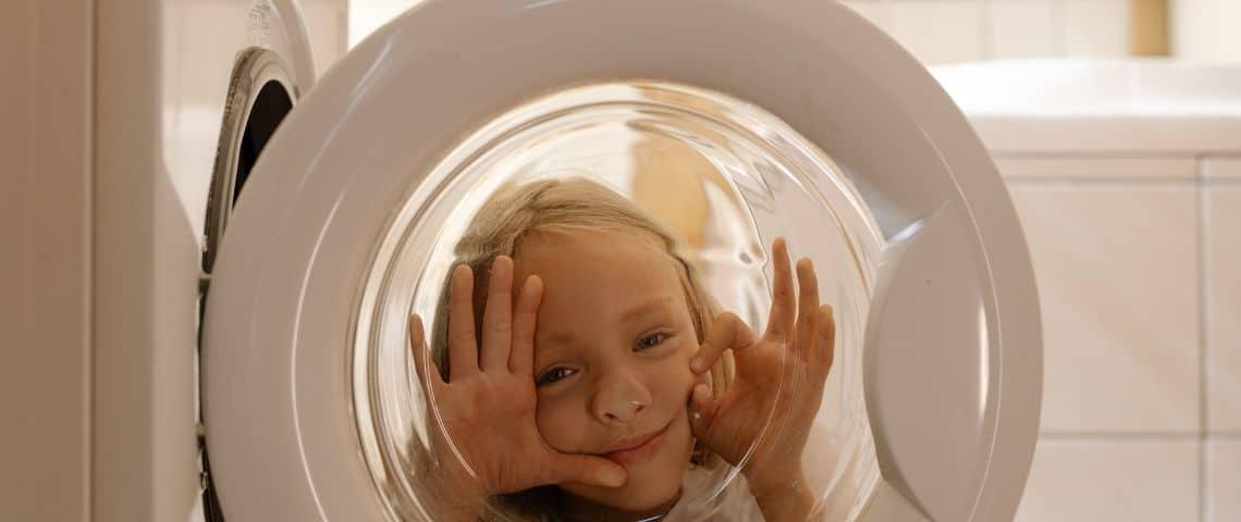 Petite fille faisdant coucou derrière la vitre du hublot d'une machine à laver
