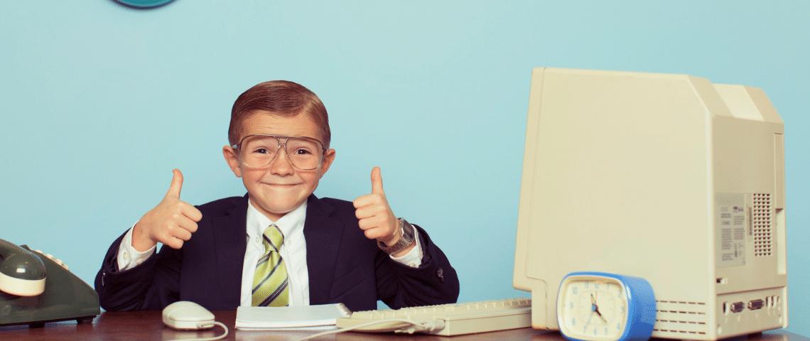 Un enfant en costume noir assis à un bureau le pouce en l'air
