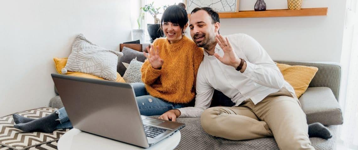 Coupl faisant un signe de la main devant un ordinateur