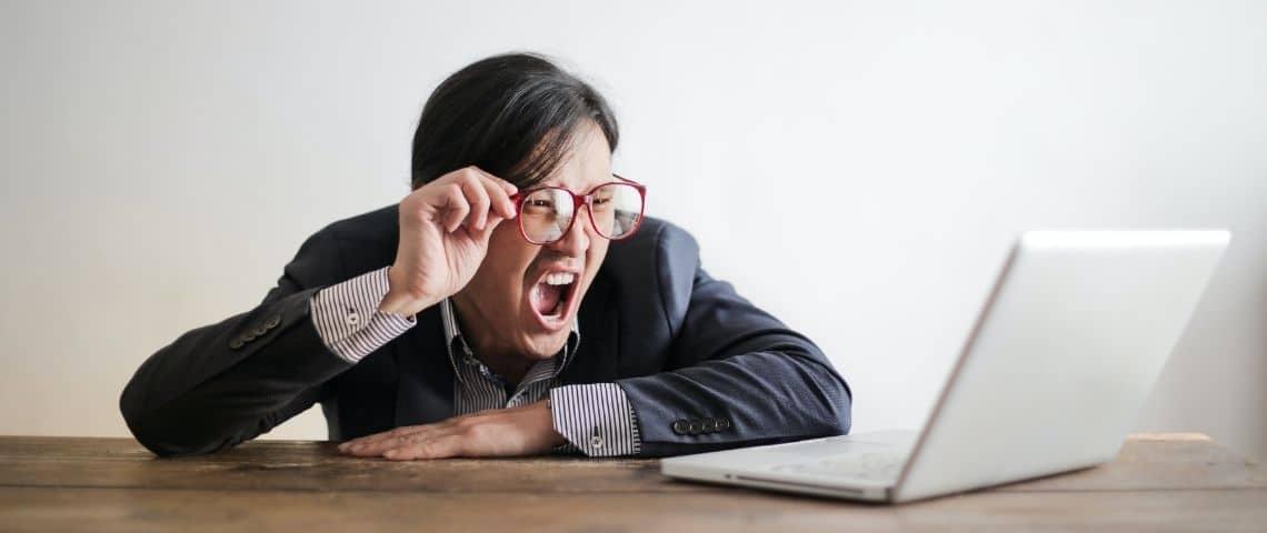 Homme en colère devant un ordinateur