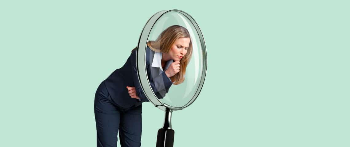 Une femme d'affaires regarde dans une loupe géante