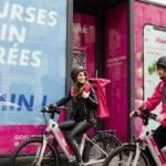 """Deux personnes à vélo, avec une affiche : """"Flink, courses enfin livrées en 10 minutes"""""""