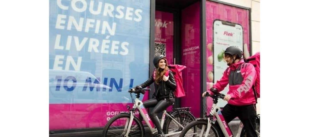 Deux personnes à vélo, avec une affiche :  - Flink, courses enfin livrées en 10 minutes -