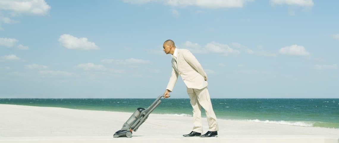 Un homme en train d'aspirer une plage de sable fin