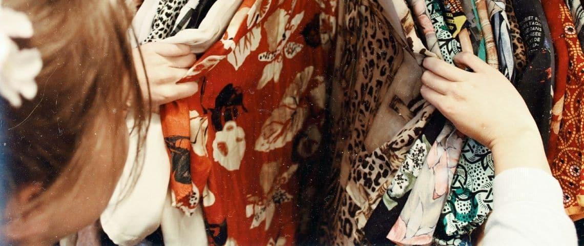 Une femme en train de regarder un portant de vêtements
