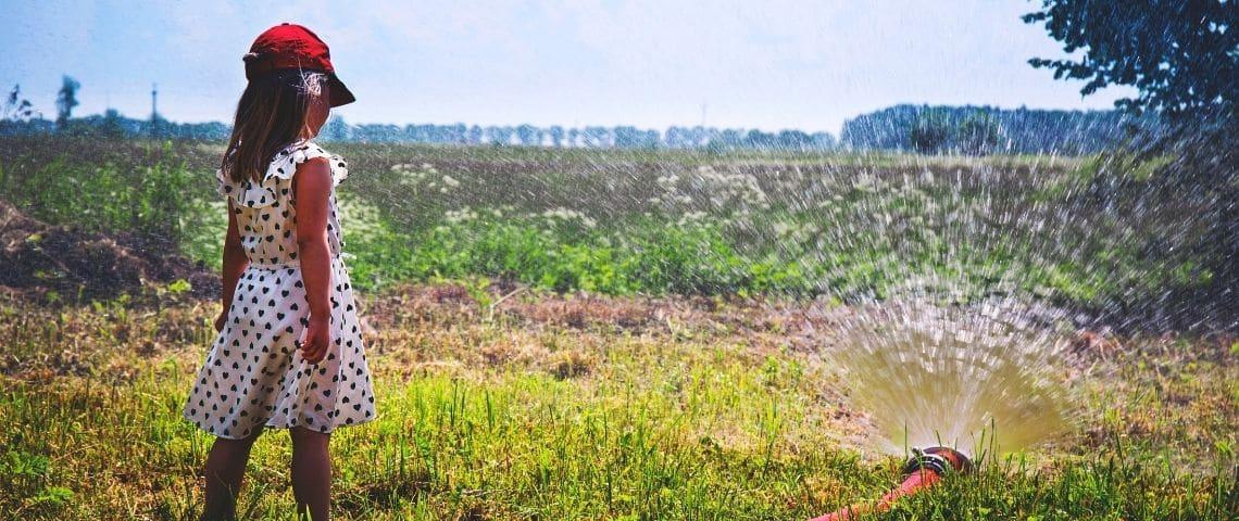 jeune fille dans un jardin avec un arrosage