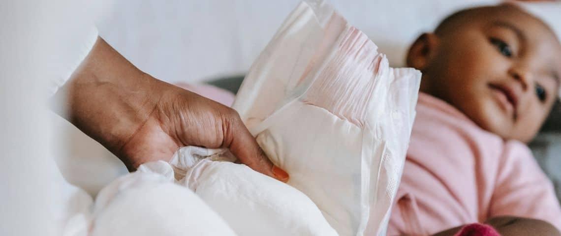 Femme tenant une couche dans ses mains avec en arrière plan un bébé allongé