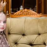 Une petite fille blonde avec une couronne sur la tête assise sur un divan vert