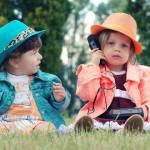 2 enfants assis dans l'herbe