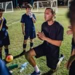 Entraineur de sport agenouillé devant son équipe de jeuens garçons
