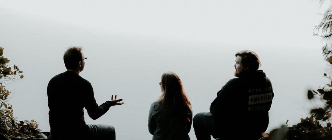 Trois personnes qui parlent au bord d'un lac