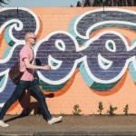 """Un homme qui marche dans la rue avec un """"tag"""" écrit """"good"""""""