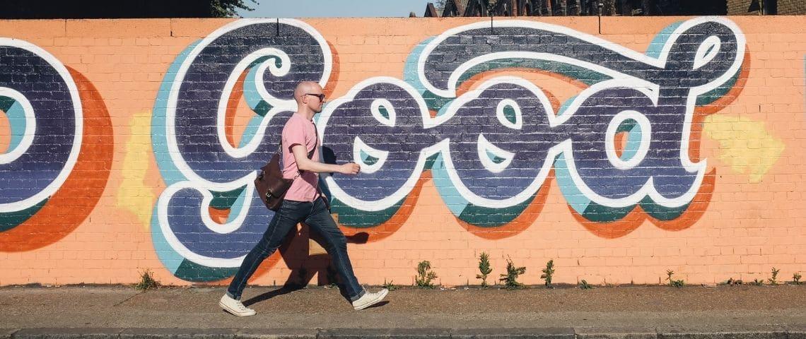 Un homme qui marche dans la rue avec un  - tag -  écrit  - good -