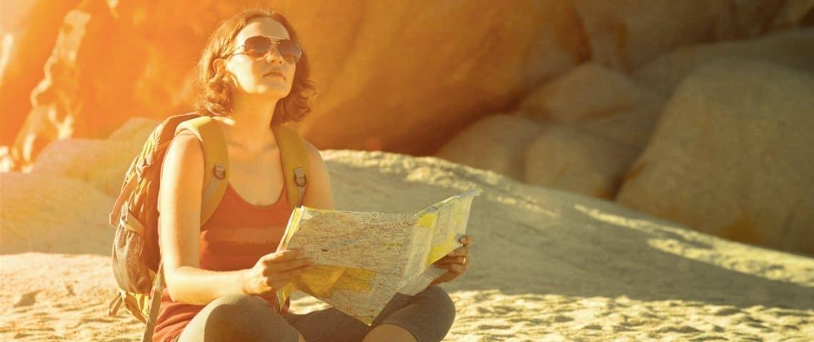 Une femme assise avec une carte et un sac à dos