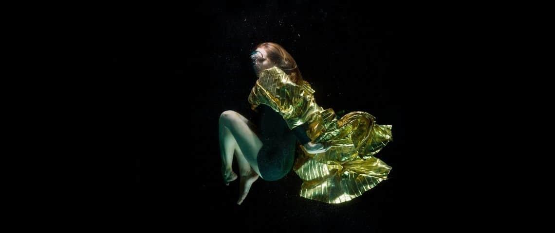 une femme dans l'eau avec un habit doré