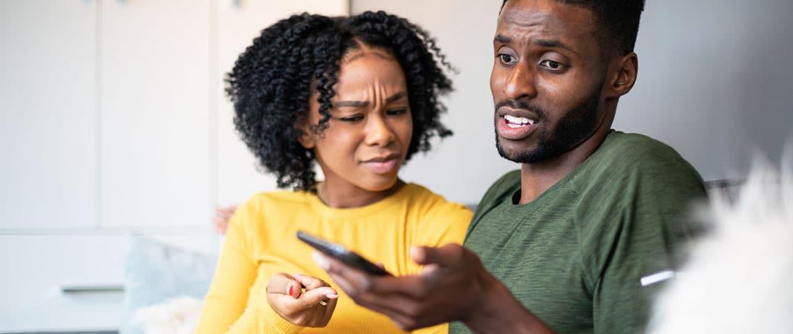 Femme métis interloquée devant le portable de son ami métis