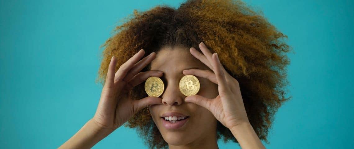 Jeunes femmes avec deux pièces de monnaie devant les yeux