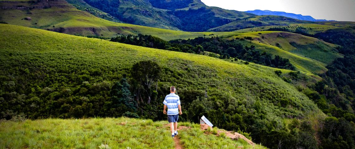 Randonneur sur colline dans un paysage naturel vaste et vert