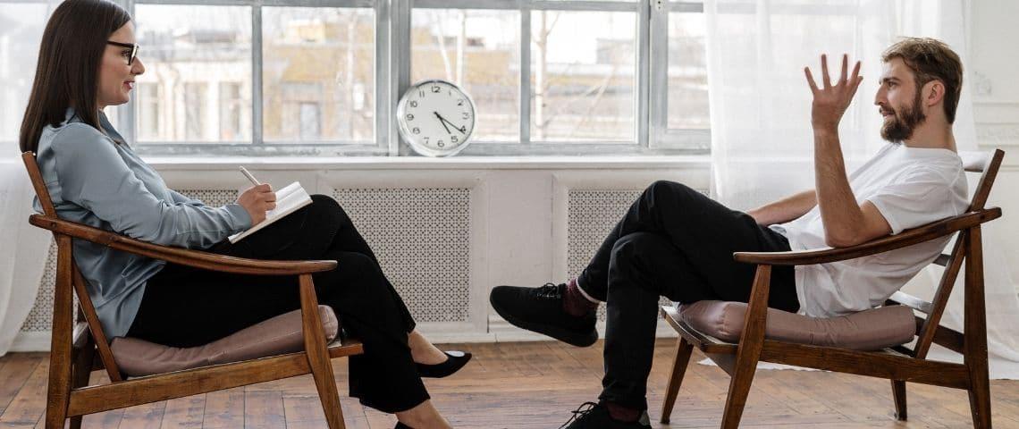 une femme et un homme assis face à face