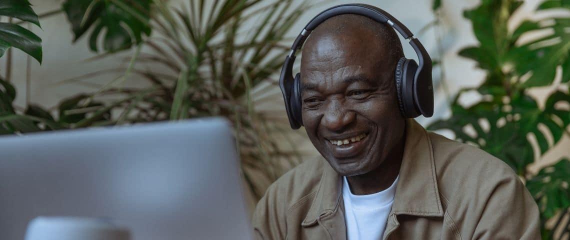 Homme avec un casque sur les oreilles, riant devant un ordinateur